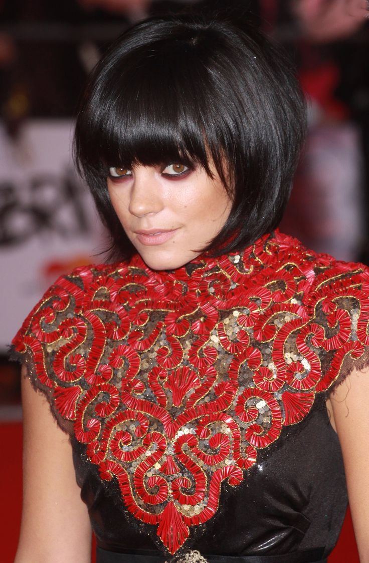 Lily Allen smoky eyes brown eyes with purple eyeshadow black hair bob bangs black dress with red beaded collar