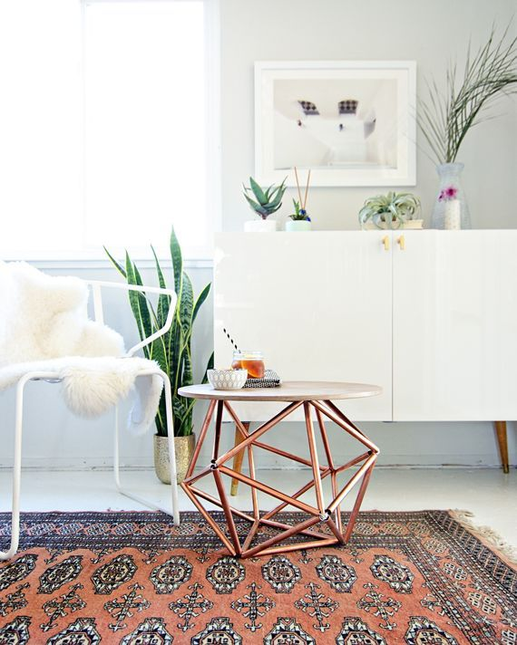 Copper pipe side table, Persian rug, white chair with sheepskin throw, and white console table