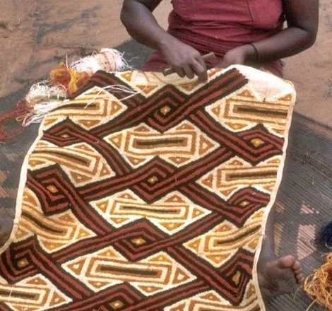 """I tessuti """"Kuba"""" provengono dal territorio Kuba, una vasta regione della Repubblica Democratica del Congo, dove vive una confederazione tribale composta da una dozzina di popoli diversi. I drappi sono tessuti a mano dagli uomini con le fibre della palma della rafia e decorati dalle donne, con tecniche diverse, che vanno dal ricamo al dipinto, all'applicazione di tessuto, conchiglie o altri materiali"""