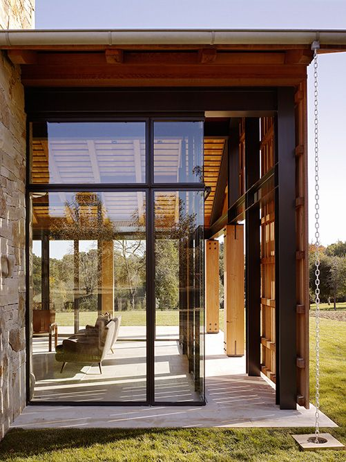 The Mountain Wood residence comprises separate buildings arranged to create a variety of complementary indoor-outdoor spaces accommodating varied living experiences. A barn frames the stone entry of the residence beyond.