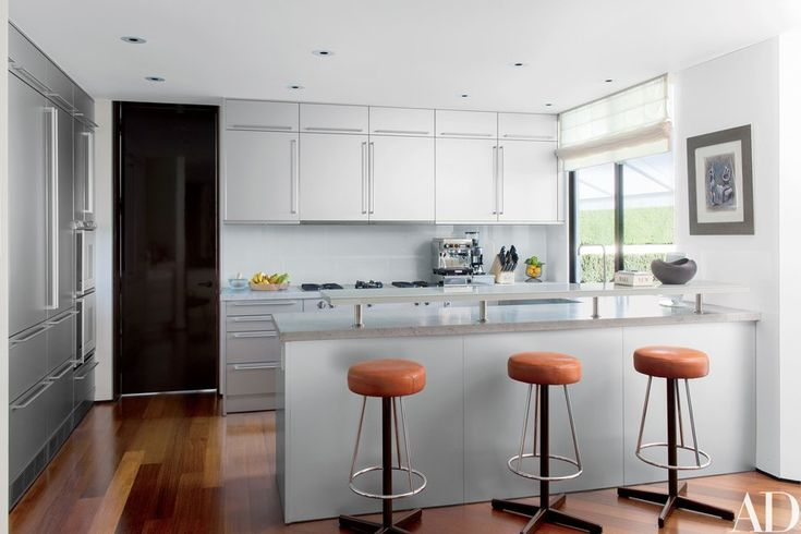 The kitchen is outfitted with Bulthaup cabinetry, a Gaggenau cooktop, Miele ovens, and a Sub-Zero refrigerator; the midcentury barstools are covered in a Moore & Giles leather.