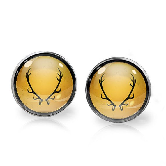 This listing is for ONE pair of House Baratheon stud earrings inspired by Game of Thrones. A perfect gift for the fangirl in your life!   These earrings measure 14mm in diameter and utilise glass domes to magnify high quality images set beneath. They are made using high quality surgical steel ear posts for sensitive ears. This listing is part of our Buy THREE get ONE free promotion. Purchase any three pairs of earrings in the promotion and receive one pair of your choice free. Please DO NOT…