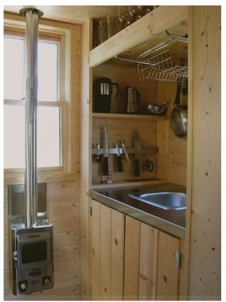 """Kitchen   [ the only thing I don't like about tiny houses: pellet/ wall/ stove heaters. For the small footprint it seems like radiant floor heat, the electric mat type, would be best. Toasty warm toes for the electricity of a low watt light bulb. Perfect for solar or, my untried invention, a """"Big Whirly"""" that is generating electric current from wind power. ]"""