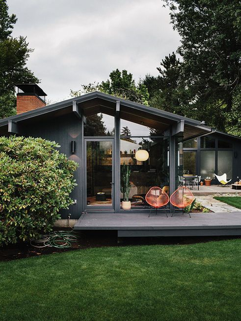 The exterior sconces are original to Zaik's 1956 design. A series of decks wraps around the house, connected by aggregate walkways that are part of a hardscape jointly designed by Helgerson's office and Lilly Villa Gardens.