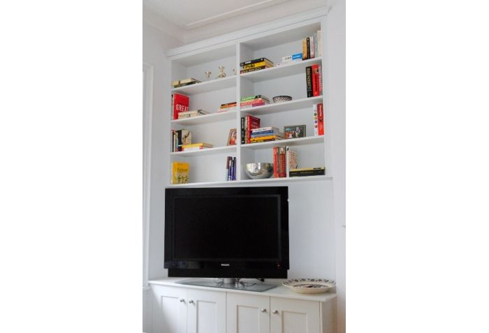 Bespoke Shaker style furniture by Anthony Mullan furniture to accommodate space either side of fireplace.