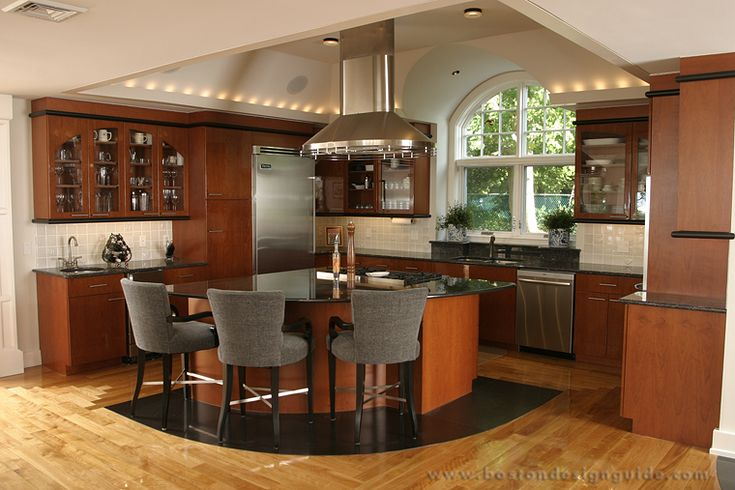 A contemporary kitchen with a triangular island and breakfast bar. The room has high ceilings with delicate recessed lighting. See how much this type of lighting costs to install.