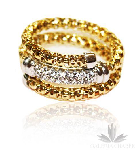 Pierścionek wykonany ze srebra próby 925, w kolorze złotym, w kształcie sprężyny. Część ozdobna wysadzana białymi Cyrkoniami, oprawa w kolorze srebrnym. Rozmiar regulowany. Szerokość wzoru to około 1,2 cm.