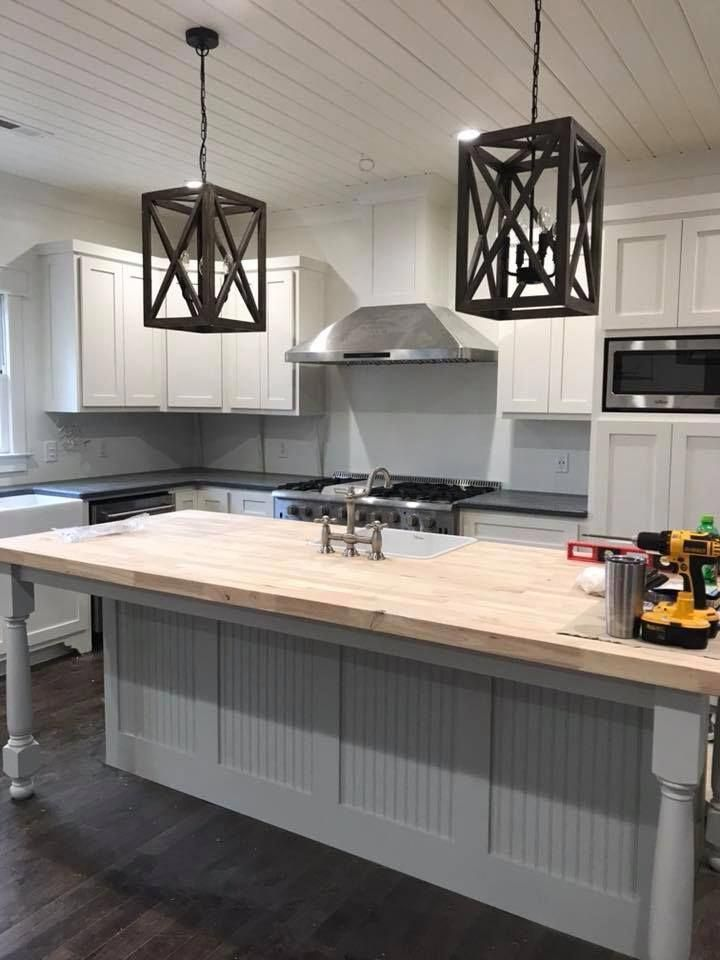 White Kitchen Cabinets With Black Counters And A Large Center Island With A Butc In 2020 Butcher Block Countertops White Cabinets White Kitchen Cabinets White Kitchen