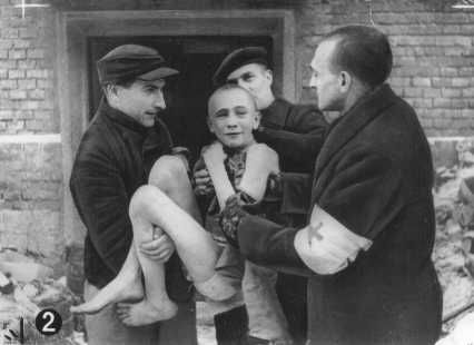 Soon after liberation, an emaciated child survivor is carried out of camp barracks by Soviet first-aid workers. Auschwitz, Poland, after January 27, 1945