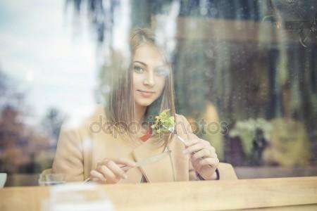 Descargar - Mujer comiendo ensalada en cafetería sentada al lado de la ventana sonriendo mirando a cámara — Imagen de stock #135305298