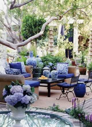 This is a great example of just having evergreen plants, but adding colour for the summer with outdoor furnishings.