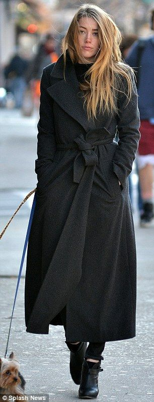 Solitary stroll: Amber cut a lone figure in her dark trenchcoat
