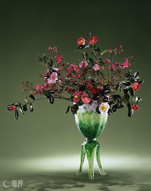 グラデーションがきれいな花器に、光沢のある濃い緑の葉を茂らせた椿とつつじで、あたたかみのある色合わせを楽しみました。花材:椿、つつじ  花器:ガラス花器(岩田久利) Enjoy the warm colors by arranging the lustrous camellia flowers and their deep green foliage with azalea in a vase marked by beautiful gradation. Material:Azalea, Camellia Container:Glass vase  #ikebana #sogetsu