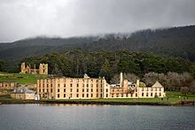 A calm body of water is in the foreground. The shoreline is about 200 metres away. To the left, close to the shore, are three tall gum trees; behind them on an incline are ruins, including walls and watchtowers of light-coloured stone and brick, what appear to be the foundations of walls, and grassed areas. To the right lie the outer walls of a large rectangular four-storey building dotted with regularly spaced windows. Forested land rises gently to a peak several kilometres back from the…