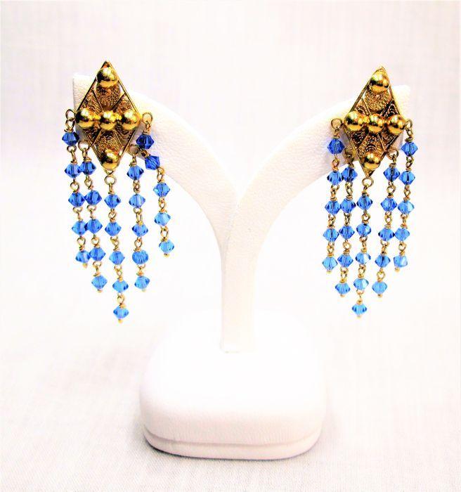 Gouden 18 karaat oorbellen met blauwe topaas. Afmetingen: lengte 50 mm - breedte: 14.8 mm - dikte: 3.2 mm.  Dikte met stekers: 13.5 mm. Gewicht: 5.9 gram. Verkeert in goede conditie, conform de foto's.  Wordt aangetekend verzonden.