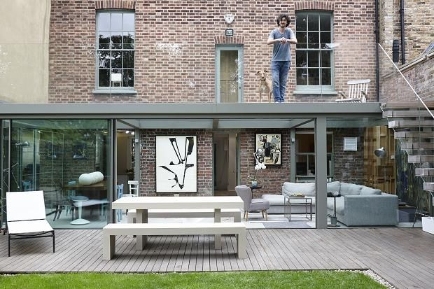 Ciprian Ilie on the glass terrace at the rear of his grade II listed Georgian home, with porcelain balls by Koji Shiraya far left. Photographed by Jake Fitzjones