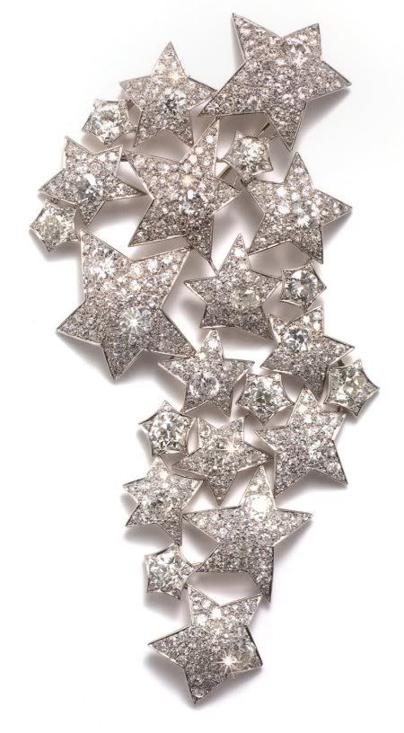 "An important platinum and diamond-set ""22 stars"" brooch by Suzanne Belperron, in the form of an articulated trail of twenty-two stars of varying size, set with brilliant-cut diamonds mounted in platinum. The ""22 star"" brooch by Suzanne Belperron, epitomises the glamour, style and charisma of an outstanding designer. Working originally for Boivin and then in partnership with Bernard Herz, Belperron's clients included the  Duchess of Windsor and Frank Sinatra. Paris, circa 1935, 12.2 cm in…"