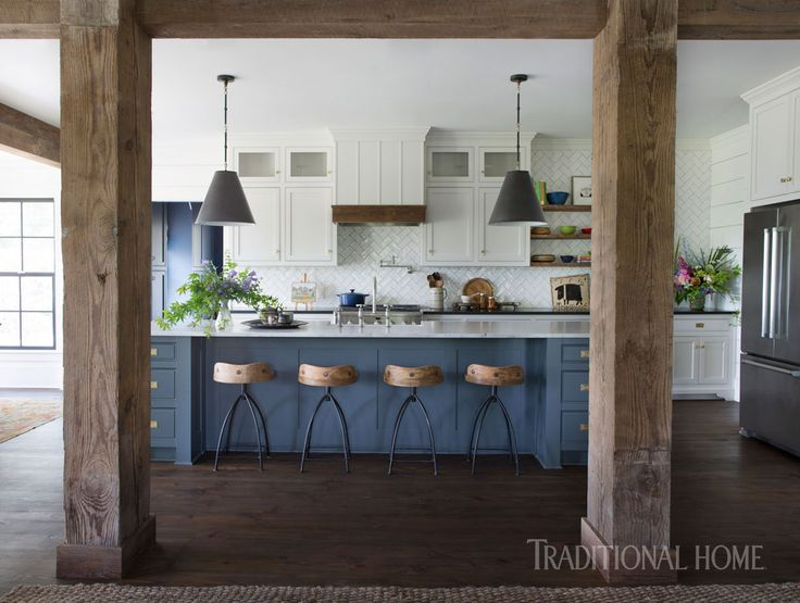 An open kitchen benefits from the warmth of reclaimed beams mixed with modern appliances. The hanging pendants are by Visual Comfort. - Photo: Sarah Dorio / Design: Cloth & Kind