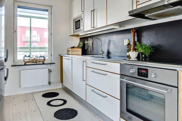 Köket är stilrent och inger en exklusiv känsla. Vita tidlösa köksluckor från välrenommerade Ballingslöv snyggt varvat mot rostfri bänskiva i stål (Norditech) och rostfri blandare från Strand.