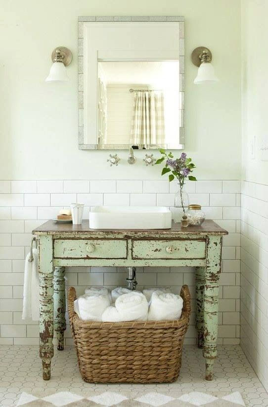 Table sink with exposed plumbing and a giant basket for towels underneath. PERFECT! except replace the towels with toilet paper probably, unless we do a TP storage thing above the actual toilet. I would also do towel rings above the table with the lights due to smaller space issues