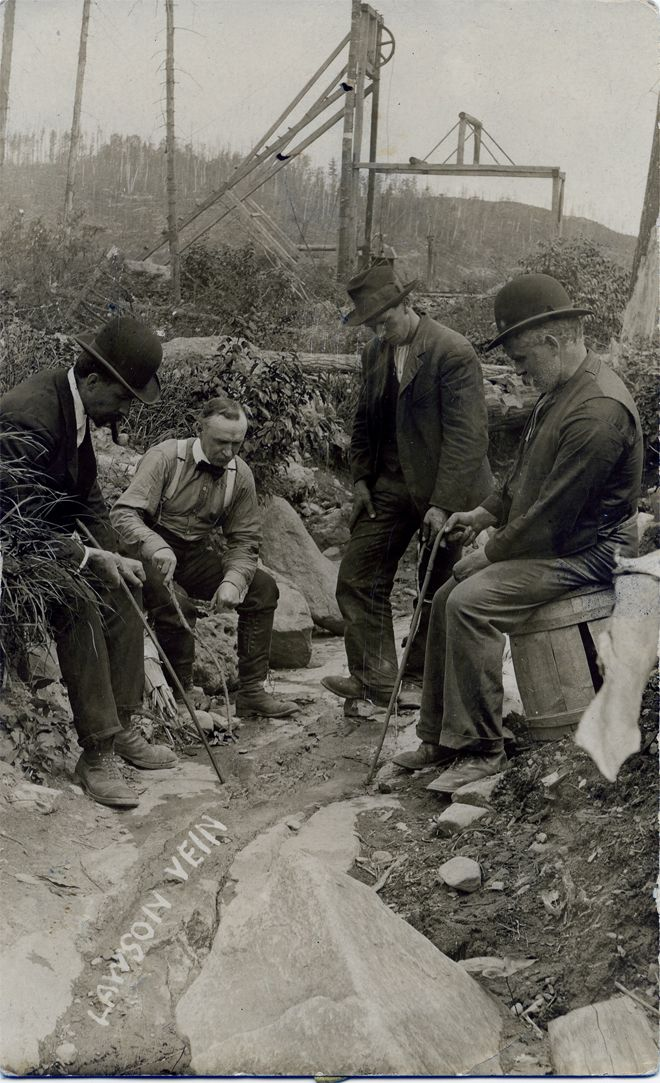 A photograph of four men sitting and examining the famous silver sidewalk.
