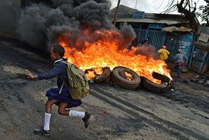 A schoolgirl runs past a burning barricade in the Kibera slum during a demonstration by opposition supporters calling for a change of leadership