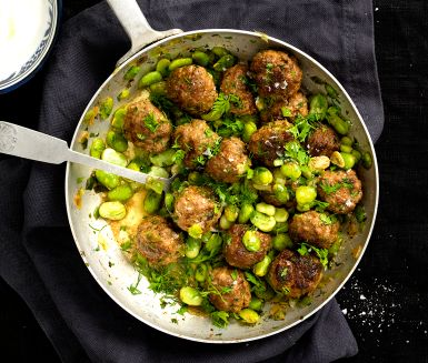Meatballs together with fava beans and scallions ...