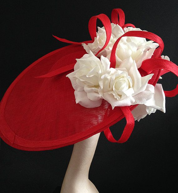 Bright red 19inch sinamay saucer, with bright white silk roses and red sinamay loops.  Fantastic statement piece. Hand blocked shape.  Sits almost on top of the head with the detail being to the right hand side of the headpiece, mounted on a thin 3mm silver headband with a comb for added security - or can be a comb and hat elastic if you prefer  Great for events such as a wedding, race meetings such as Royal Ascot, Cheltenham, Ebor, Goodwood, Melbourne Cup, Kentucky Derby or any hat wearing…