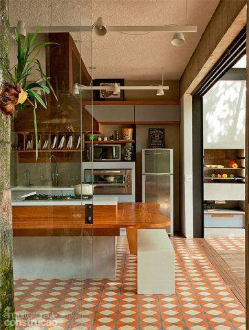 A ilha gourmet tem base de concreto e bancada de Corian (DuPont) com cooktop. Ao redor dela, uma área de apoio prevista no projeto de marcenaria acomoda os convidados. Arredondadas, as bordas facilitam a circulação à sua volta. Na divisa dos ambientes, as réguas corrigem o desnível criado pelos trilhos da porta de correr, encaixando-se como um quebra-cabeça no vão entre o piso de ladrilhos (Brasil Imperial) e o deck (Hydrotech). Para fechar os painéis deslizantes, é preciso retirá-las.