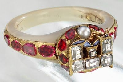 """This is the locket ring of Queen Elizabeth I.  It was removed from her finger at her death on 3-34-1603. It is mother-of-pearl. The band is set in rubies, the """"E"""" contains 6 diamonds set in a blue enamel """"R"""". A pearl is also seen. The hinge opens to reveal an enamel portrait of the queen c. 1575,  Also that of an unnamed woman.  The costume of the woman suggests it may be Edwardian and that of her mother, Anne Boleyn."""