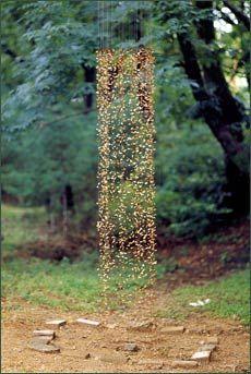 "Cornelia Konrads. ""remember next spring"" (2003) . Geumgang International Nature Art Exhibition, Gongju, (Korea) Installation reflecting the shape of a memorialstone on a place nearby . mapleseeds, steerope, fishingline, wire 2.8 x 0.7 x 0.6 m"
