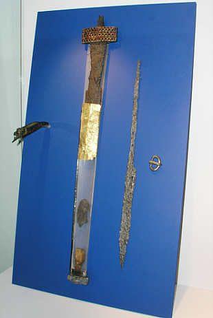 """Spatha y ajuar de la tumba de Altlussheim (distr. Rhin-Neckar, Bade-Wurtemberg, Alemania). Mediados del siglo V. Guarda ancha, de tipo """"asiático"""", de bronce decorada en la parte delantera con un aplique de oro con decoración polícroma cloisonée (tabicada) de granates. Vian recubierta de chapa de oro. Karlsruhe, Badische Landesmuseum. Inv. nº C 11401 a-e."""