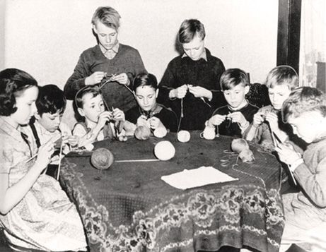 Knitting was taught in many Canadian classrooms during World War Two. Students organized Red Cross sewing rooms and sewed and knit articles for servicemen, civilians in bombed areas, and orphaned British children. In this photo from the Canadian War Museum, there is only one girl on the left; the rest are boys.