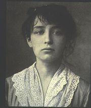 Head and shoulders of a young, dark haired woman looking downward.