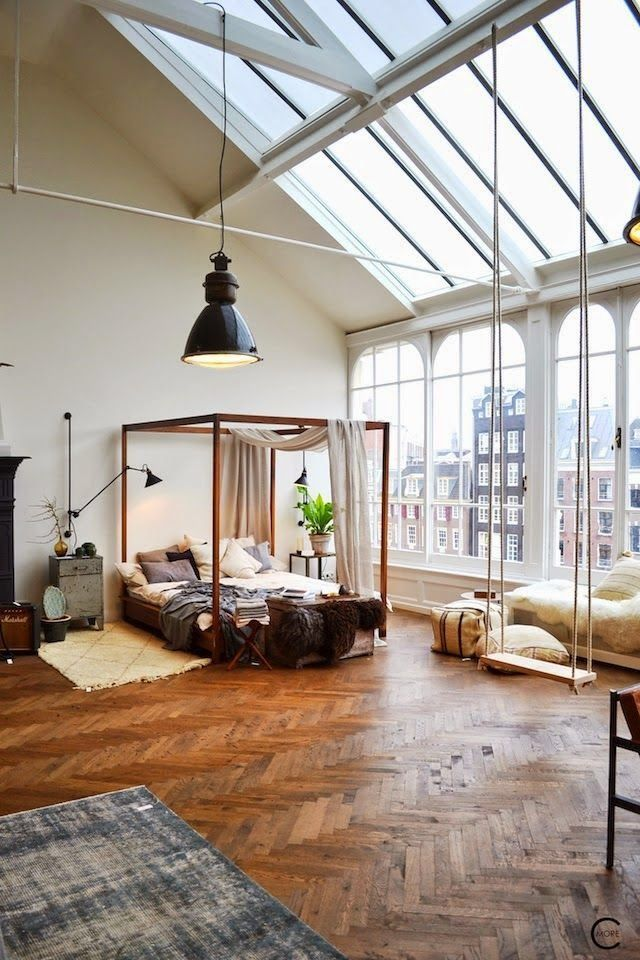 Wooden canopy bed inside a beautiful New York studio with big windows, plants, sheepskin rugs, all displaced on mahogany wooden floors