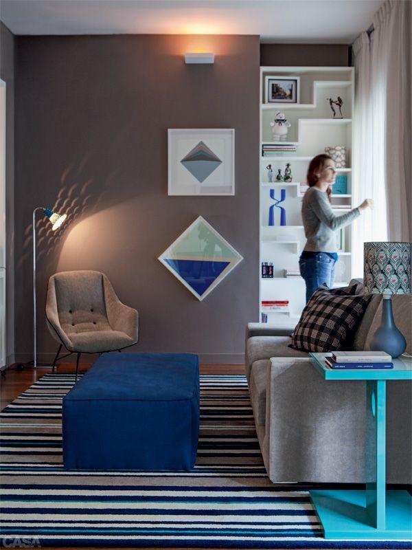 Um dos três quartos da planta se abriu para o estar, acolhendo o home theater. O azul do tapete (Punto e Filo) e das gravuras de Hércules Barsotti (1914-2010) cria pontos de destaque. Poltrona e luminária da Filter. Estante executada pela Madeirarte.