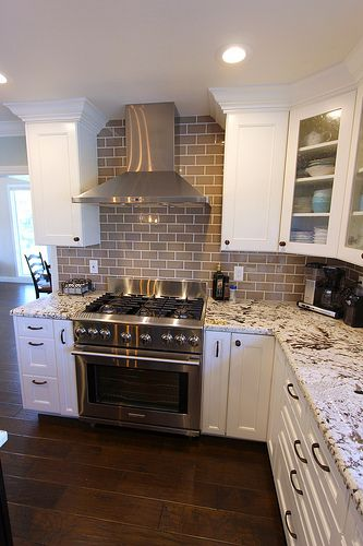 White cabinets with neutral granite and wood floors