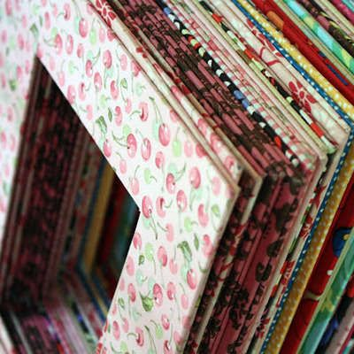 Who knew cardboard could be so versatile! Love this idea!  Why use a plain-Jane picture mat from the craft store, when you can customize one with fabric?  Thin cardboard, like that from a cereal box or notepad backing is perfect for this.  Just cut it to the appropriate size and use spray adhesive and Mod Podge to add your fabric.  It will frame your photos beautifully.