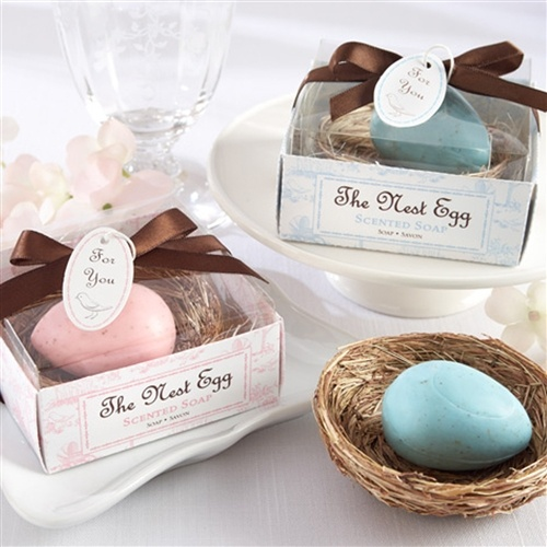 """The Nest Egg"" Scented Egg Soap in Nest (Pink or Blue)  Available in pink or blue, these cell-wrapped pleasantly scented soap favors have tiny, brown speckles on them and come nestled in a lifelike bird's nest that is sitting on natural, shredded raffia. They are presented in a clear-top gift box with either a pastel-blue or pink base with Toile print of baby carriages, birds, nests with eggs, trees with tiny nests and happy homes and are finished off with a chocolate-brown satin ribbon and…"