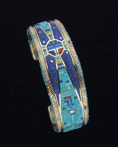 A Navajo bracelet Raymond Yazzie.   inset with over 650 individually cut and polished inlays of coral, turquoise and lapis lazuli, worked to depict a traditional Navajo Yei figure, standing with prayer feathers hung from his arms, placed on a mosaic background that tapers towards a central mask resembling a Hopi Sun kachina, complemented by a carved lightning bolt, raincloud motif, and horned globe