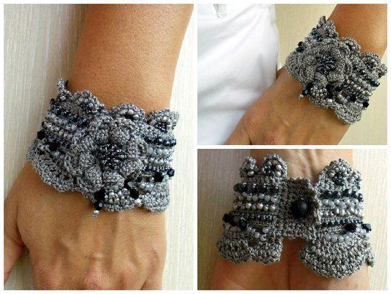 Eine einzigartige Handarbeit häkeln-Manschette.  Das Armband ist mit 3D Blume mit vielen Perlen verziert.  Hauptfarben sind Silber.  Die Perlen unterscheiden sich in Größe und Farbe.  Ich habe diese Manschette mit eine freie Form-häkeln-Technik und viel Phantasie, es ist also absolut einzigartig und kann nicht reproduziert werden, ein zweites Mal.  Das Armband kann mit kaltem Seifenwasser und nur von hand gewaschen werden. Auf einer flachen Oberfläche trocken geschützt vor der Sonne…