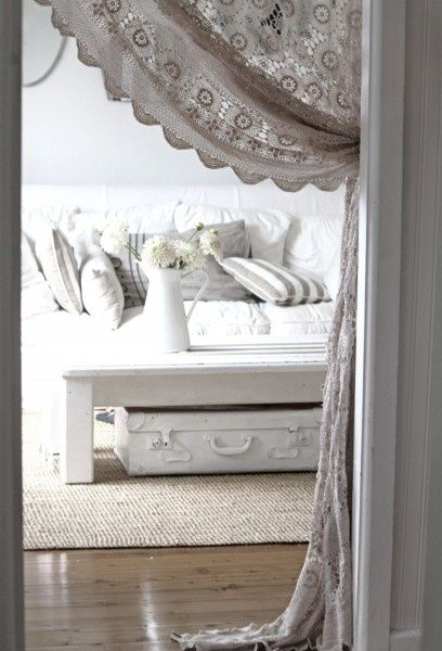 Light, white and bright with a sisal rug from A Beach Cottage  Love suitcase under coffee table for storage