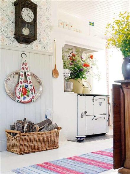 Den gamla vedspisen från Husqvarna värmer upp  köket och gästrummet  vintertid. Vedkorgen är från Ikea och den stora brickan är inköpt i antikaffär. Den lilla brickan kommer från Vietnam. Uret är ärvt.