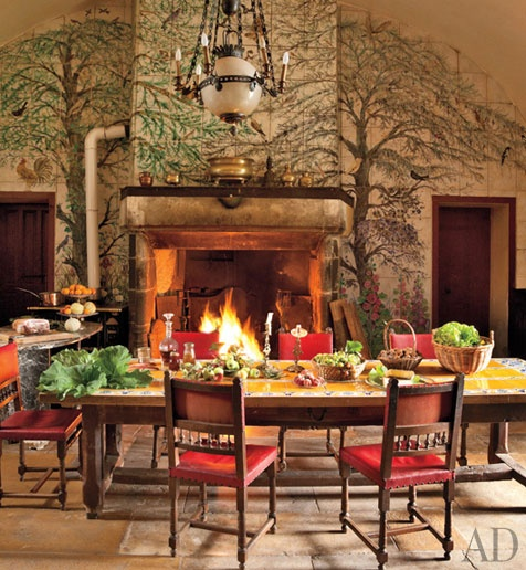 Imagine having an eating space in the kitchen like this. The trees around the fireplace are created with hand-painted tiles. Love the antique tile-top table.