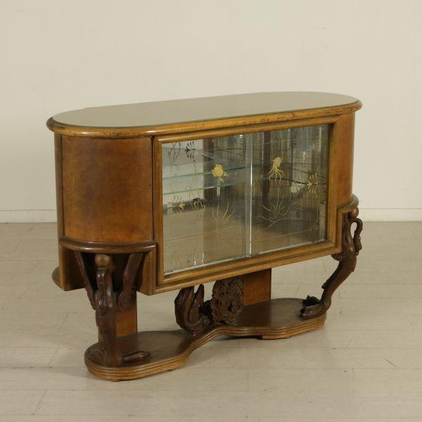 Mobile bar; legno impiallacciato radica, gambe in legno intagliato, ante scorrevoli in vetro decorato, vetro retro trattato sul piano. Buone condizioni; presenta piccoli segni di usura.