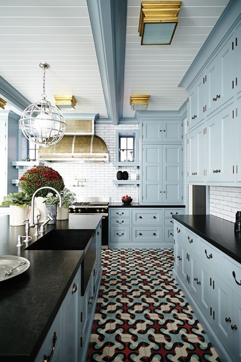 light blue kitchen cabinets, black countertop, tile floor, brass flush fixtures + range