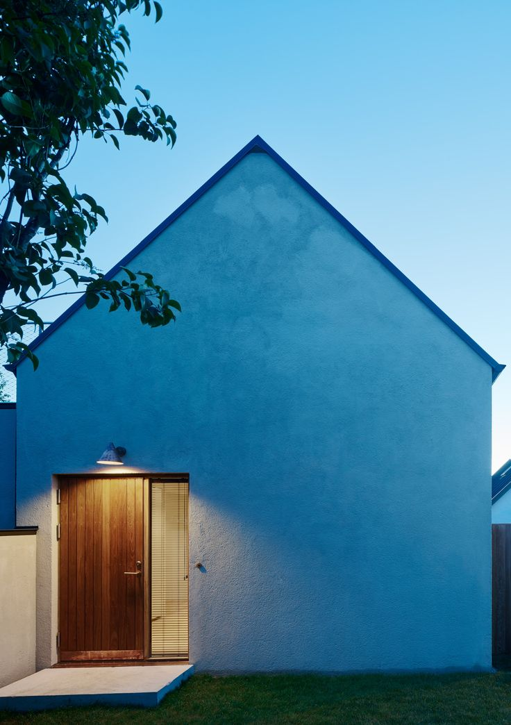 A gabled wall provides the entrance to this holiday home in a Swedish coastal village, which also features rooms arranged around a garden and cherry tree