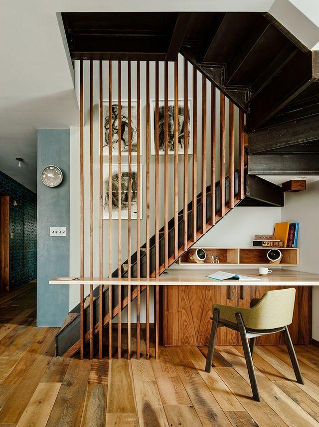 Ce garde-corps d'escalier en bois apporte de la hauteur au coin bureau grâce à son design longiligne.