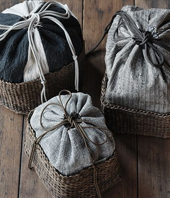 At her studio in the ancient city of Nara, Mieko Tsuchiya creates beautiful, functional textiles for the home in a pallete of subtle, muted tones. Tsuchiya's elegant kinchaku kago ( drawstring bag) are the result of her collaboration with two other artisans, one specializing in basket weaving and the other fashioning the drawstring that pulsl together the hand woven fabric.