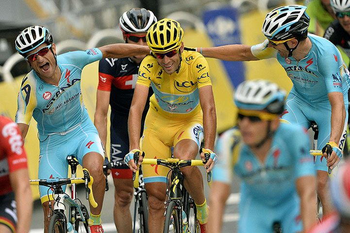 Credit: Lionel Bonaventure/AFP/Getty Images The 2014 overall winner Italy's Vincenzo Nibali is congratulated by his Astana's teammates as he crosses the finish line on the Champs-Elysees at the end of the 137.5 km 21st and last stage of the 101st Tour de France.